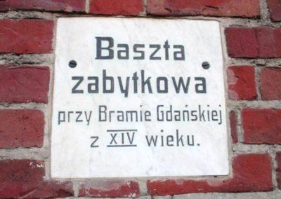 Tablica informacyjna wmurowana w ścianę Baszty Gdańskiej (Szewskiej)